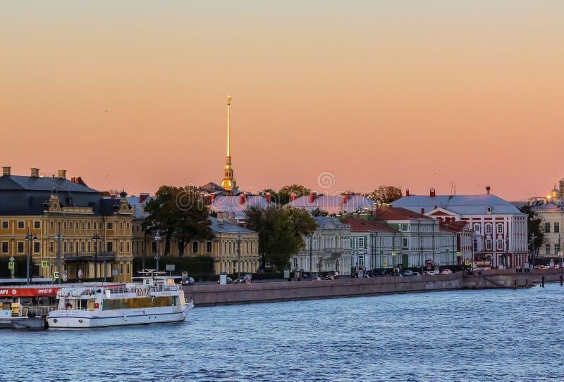 Заход солнца в Санкт-Петербурге над рекой Neva с взглядом обваловки дворца и шпиля крепости Питер и Пол стоковые изображения