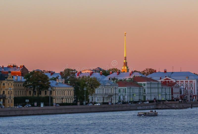 Заход солнца в Санкт-Петербурге над рекой Neva с взглядом обваловки дворца и шпиля крепости Питер и Пол стоковое фото