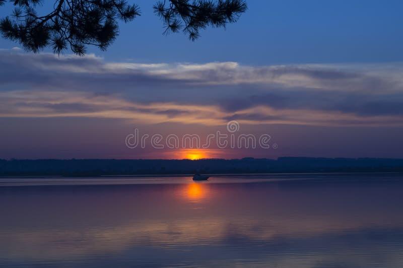 Заход солнца над рекой, в расстоянии вы можете увидеть шлюпку стоковое изображение rf
