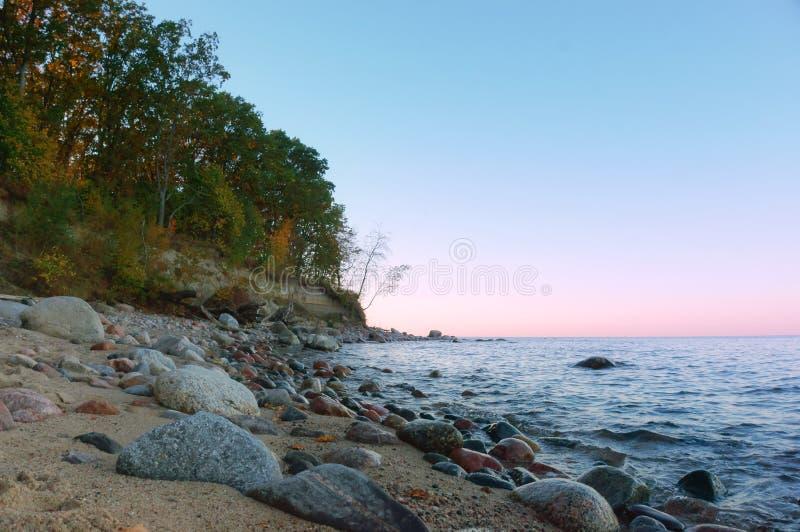 Заход солнца на скалистом seashore стоковое изображение rf