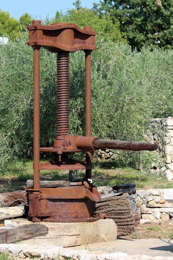 Заржаветая сильная машина прессы оливкового масла года сбора винограда металла установленная на конкретном учреждении используемо стоковые изображения rf