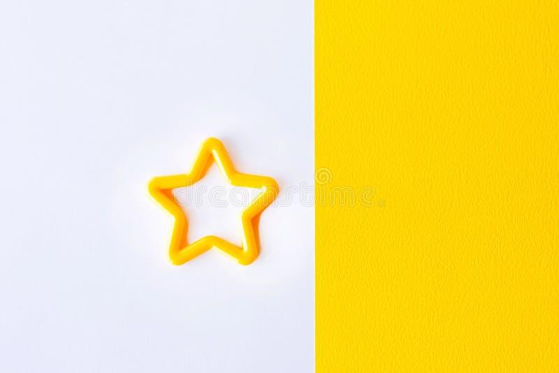 звезда на белой и желтой предпосылке Плоское положение Скопируйте космос для текста стоковые фото