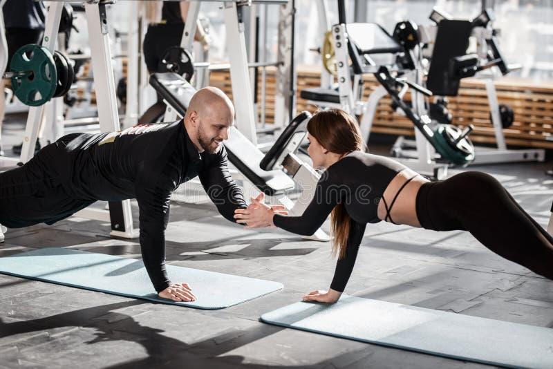 Зверский атлетический человек и молодая худенькая девушка одетые в черных одеждах видов делают планку держа рука об руку в стоковое изображение rf