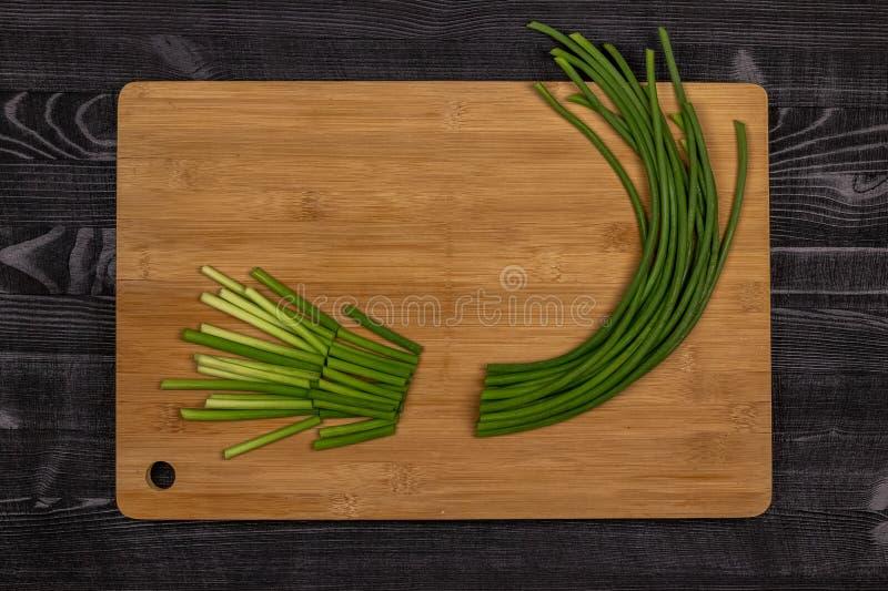 Зеленые всходы чеснока или копиь чеснока на разделочной доске подготовленной для резать как часть процесса делать чеснок стоковая фотография rf