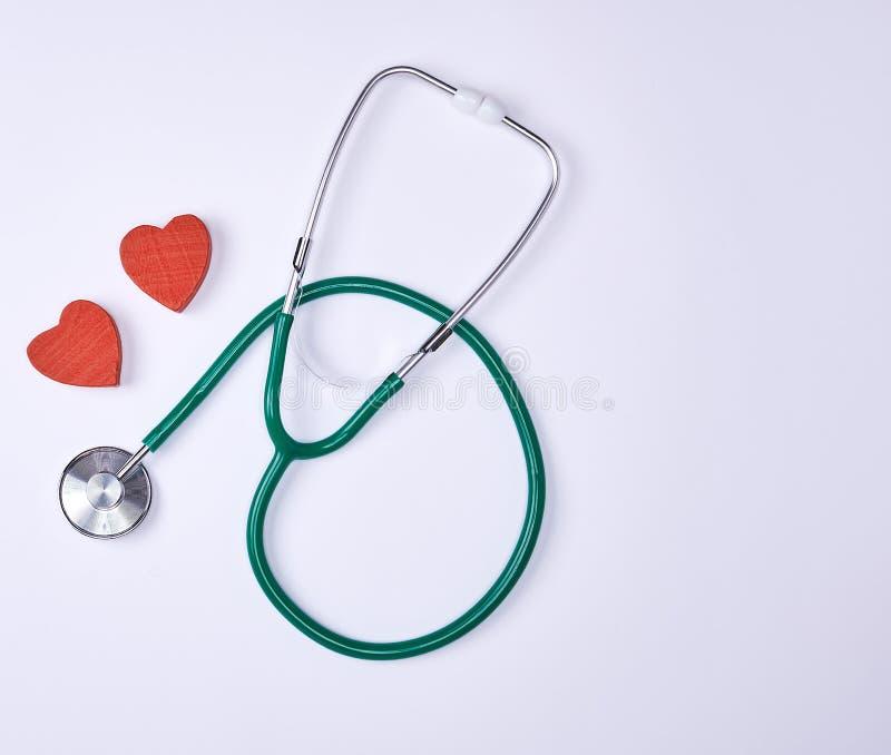 Зеленый медицинский стетоскоп и 2 красных декоративных сердца стоковые фотографии rf