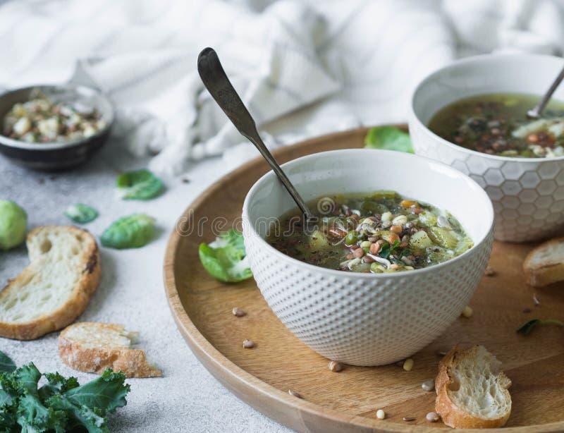 Зеленый суп vegan овоща от keil, ростков Брюсселя, цукини, лук-порея с различными прорастанными семенами и ростков с гренками дал стоковые фотографии rf