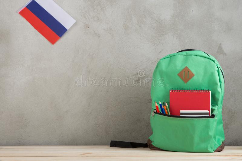 зеленый рюкзак, флаг России, ведомство канцлера и тетради против стены цемента стоковое изображение