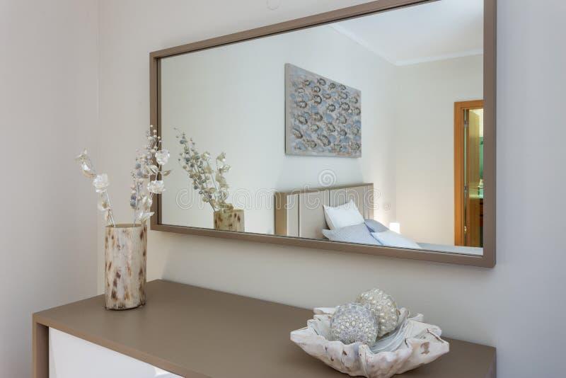 Зеркало в спальне отражает кровать Оформление современно стоковое фото