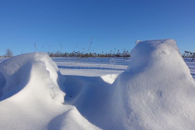 зима белизны снежинок предпосылки голубая Аннотация Смещения снега на предпосылку голубого ясного неба, ровные переходы линий све стоковая фотография rf