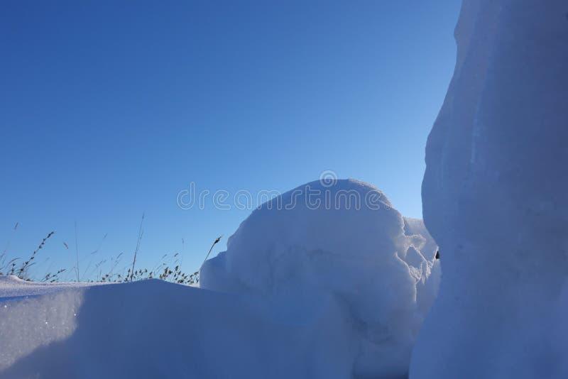 зима белизны снежинок предпосылки голубая Аннотация Смещения снега на предпосылку голубого ясного неба, ровные переходы линий све стоковые изображения rf