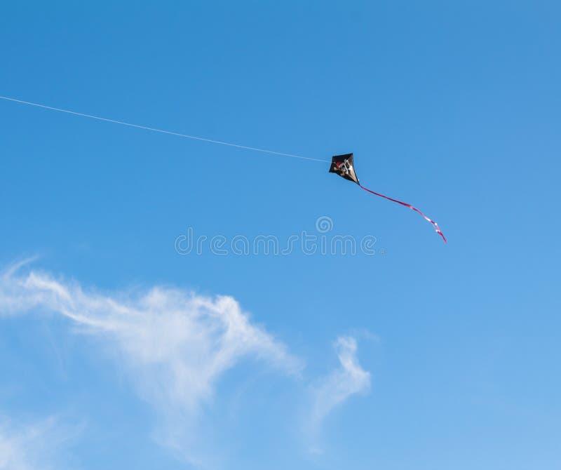 Змей флага пирата черного змея в небе ясности воздуха стоковая фотография