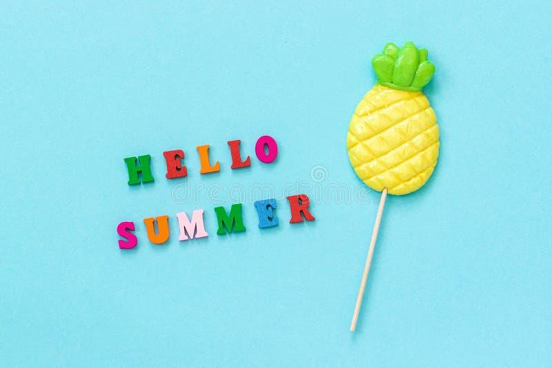 Здравствуйте текст лета красочный, леденец на палочке ананаса на ручке на голубой бумажной предпосылке Каникулы концепции или взг стоковые изображения rf