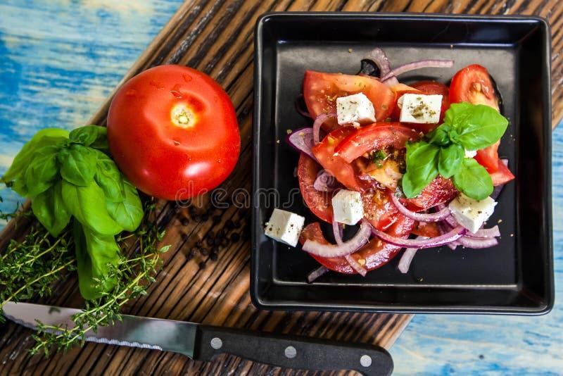 Здоровый греческий салат с томатами на черной плите над деревянной доской стоковая фотография rf