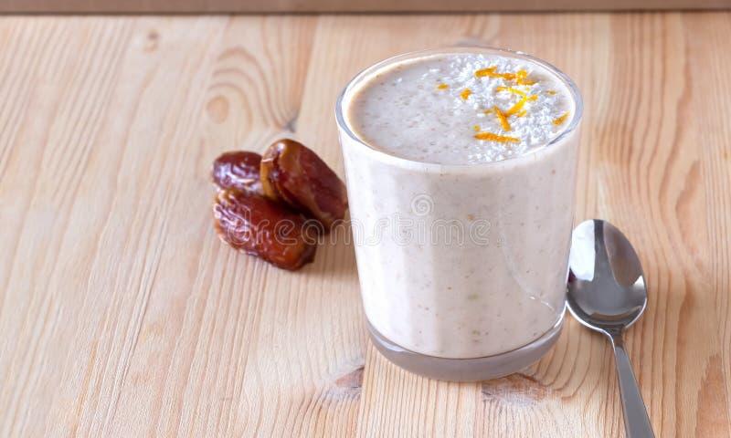 Здоровый органический smoothie молока даты, банана и яблока напудрил shredded кокос и завтрак диеты оранжевого пыла свежий стоковое фото rf