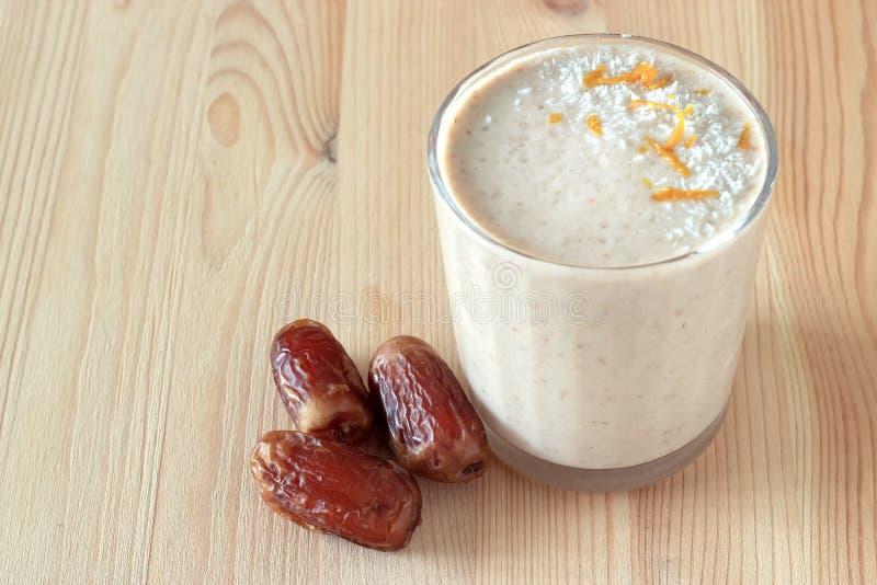Здоровый органический smoothie молока даты, банана и яблока напудрил shredded кокос и завтрак диеты оранжевого пыла свежий стоковая фотография