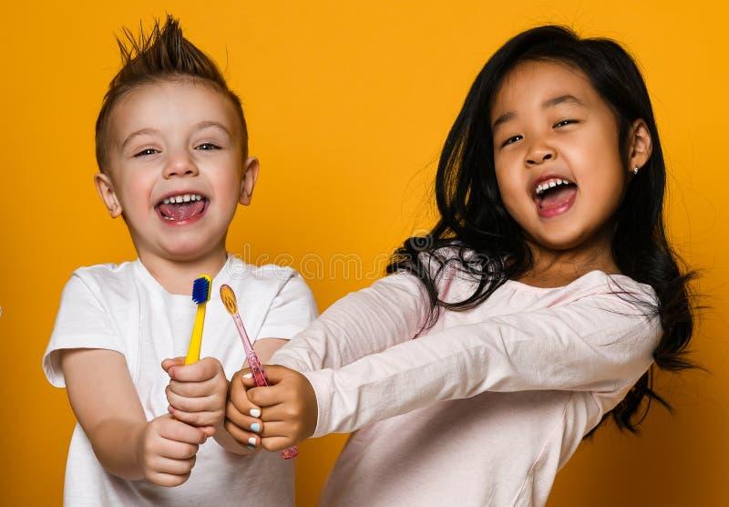 зубоврачебная гигиена счастливые маленькие милые дети с зубными щетками стоковое фото