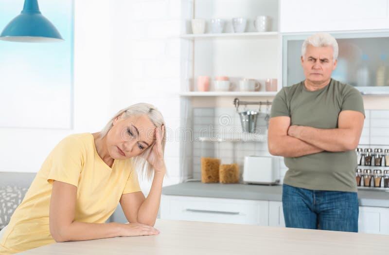 Зрелые пары споря в кухне отношение стоковая фотография rf