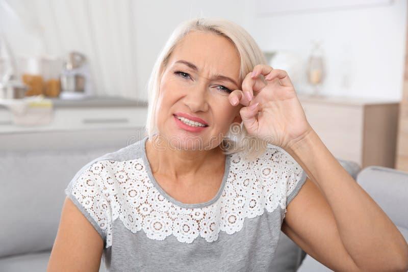 Зрелый глаз затирания женщины дома стоковые фотографии rf