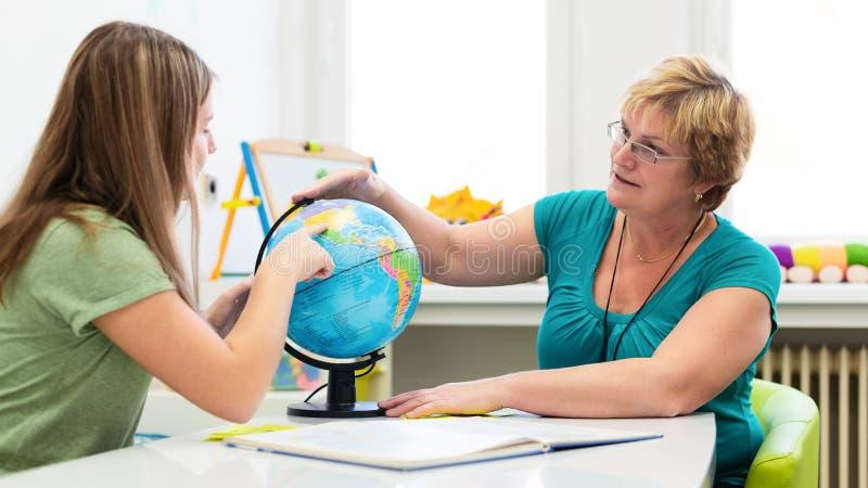 Зрелый женский терапевт работая с девочка-подростком с затруднениями в учебе Частная встреча обучения землеведения стоковые изображения rf