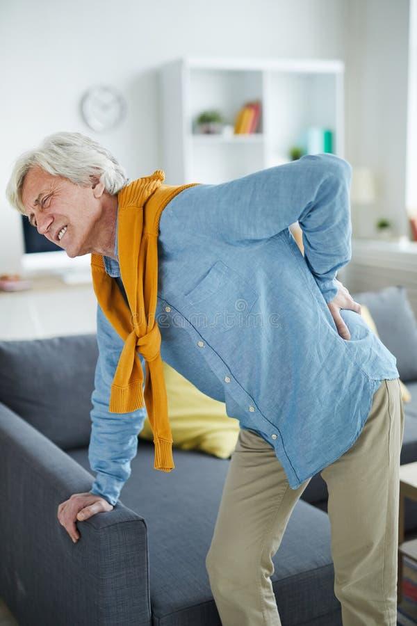 Зрелый человек страдая от боли в спине стоковое фото