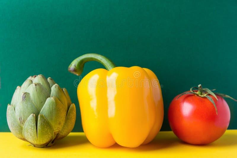 Зрелый органический томат capsicum артишока овощей на предпосылке duotone темной ой-зелен желтой Здоровый завод основал диету сре стоковое фото rf