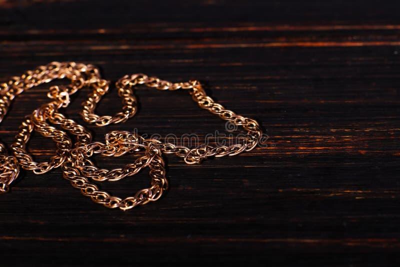 Золотая цепь сплетя не, на деревянной предпосылке Макрос, мягкий фокус стоковые изображения rf