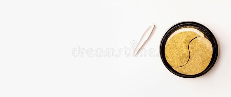 Золотые заплаты глаза в опарнике с щипчиками Заплата гидрогеля Анти- вызревание и подниматься Забота кожи стороны Разводить водой стоковое изображение
