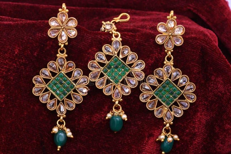 Золотые ювелирные изделия - серьги вычуры дизайнерские для моды женщины с главным аксессуаром стоковое фото