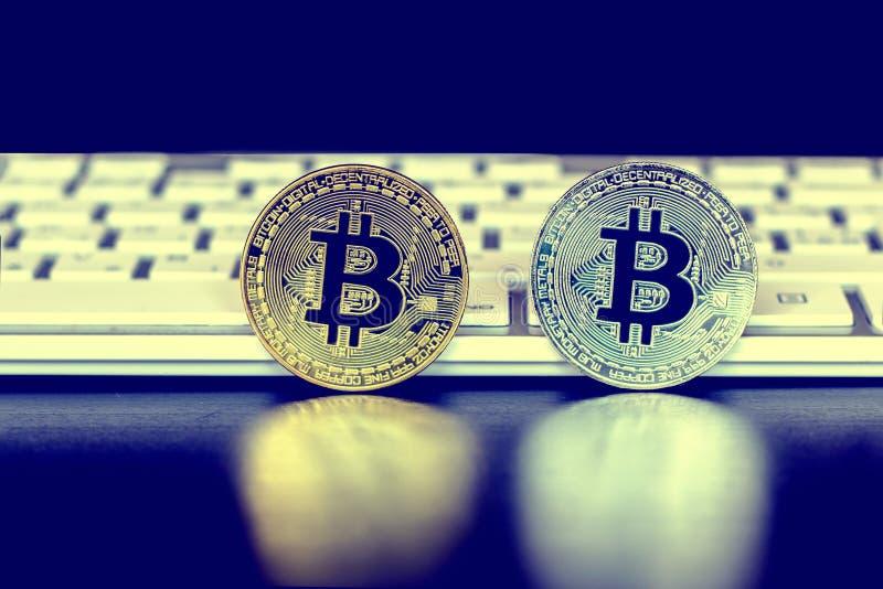 Золото и серебряные монеты стоек bitcoin на черной предпосылке перед белыми клавиатурами стоковые фото