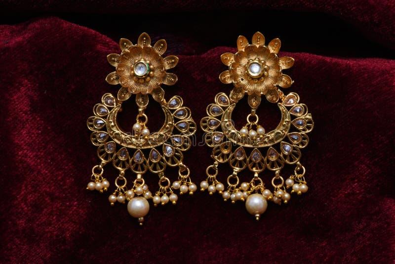 Золото покрыло ювелирные изделия - изображение макроса серег вычуры дизайнерское золотое длинное стоковая фотография