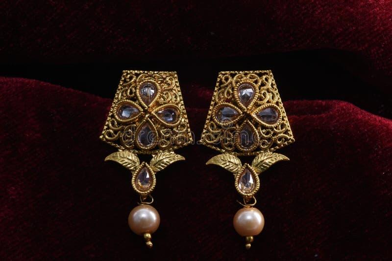 Золото покрыло ювелирные изделия - изображение макроса серег вычуры дизайнерское золотое стоковая фотография rf