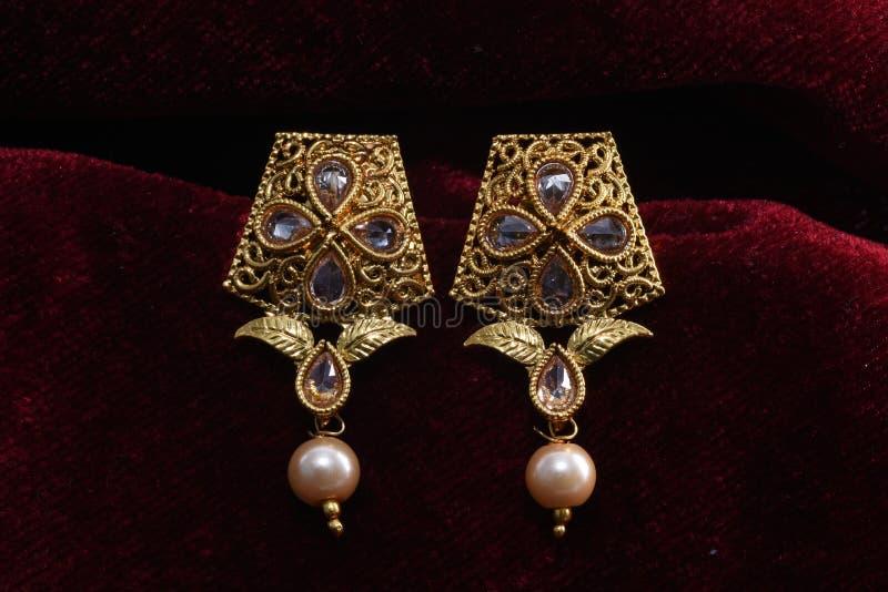 Золото покрыло ювелирные изделия - изображение макроса серег вычуры дизайнерское золотое стоковое фото