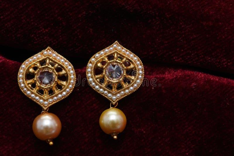 Золото покрыло ювелирные изделия - изображение макроса серег вычуры дизайнерское золотое стоковое изображение rf