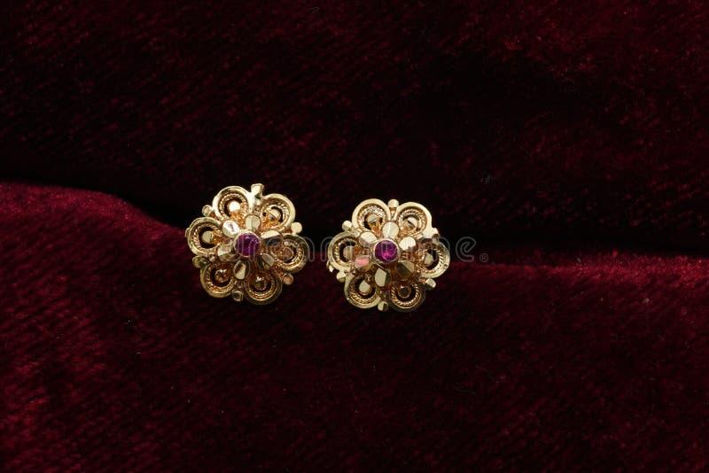 Золото покрыло ювелирные изделия - изображение макроса серег вычуры дизайнерское золотое стоковые изображения