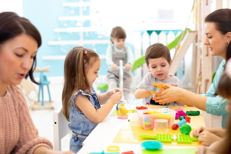 Игра теста детей в центре daycare Дети отливают в форму от пластилина в детском саде Немногое студенты замешивает глину моделиров стоковое фото