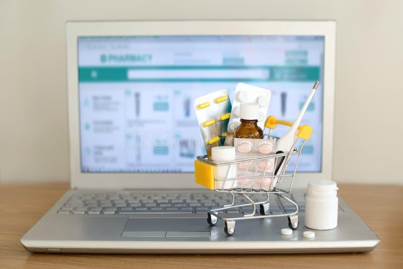 Игрушка корзины с medicaments перед экраном ноутбука с вебсайтом фармации на ем Таблетки, пакеты волдыря, медицинские бутылки, стоковые фото