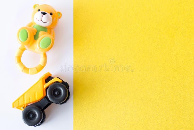 Игрушки детей на белой и желтой предпосылке Взгляд сверху Плоское положение Скопируйте космос для текста стоковые фото