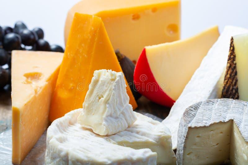 Известные европейские сыры в ассортименте, голландском красном Эдамере шарика и старых сырах с отверстиями, испанским сыром Manch стоковая фотография
