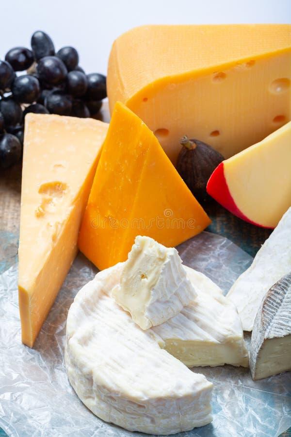 Известные европейские сыры в ассортименте, голландском красном Эдамере шарика и старых сырах с отверстиями, испанским сыром Manch стоковое изображение