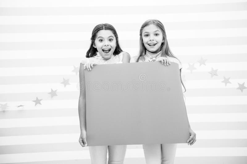 Изумительные удивительно новости Знамя объявления владением девушки Дети девушек держа бумажное знамя для объявления Дети счастли стоковое фото rf