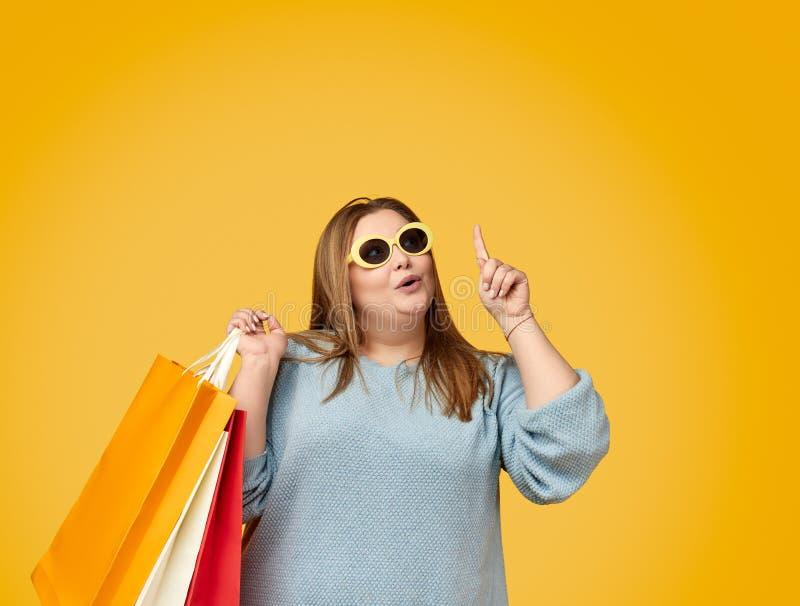 Изумленная пухлая женщина с бумажными мешками указывая вверх стоковое изображение rf
