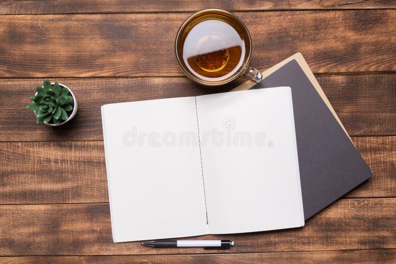 изображение взгляд сверху открытой тетради с пустыми страницами рядом с чашкой кофе на деревянном столе Подготавливайте для добав стоковые фото