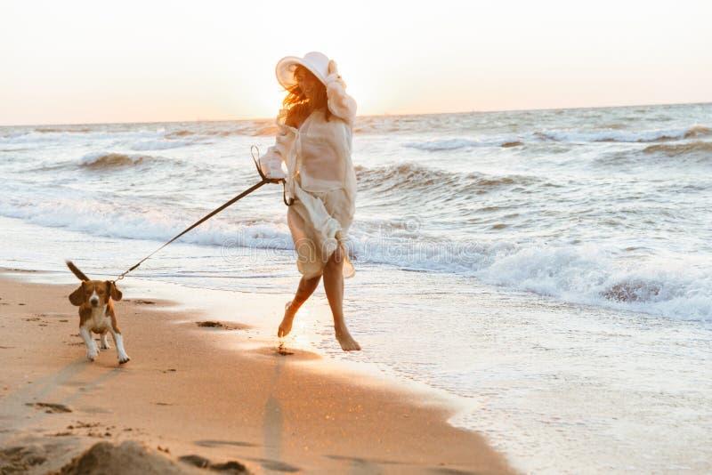 Изображение европейской женщины 20s в соломенной шляпе лета, бежать взморьем с ее собакой стоковое фото rf
