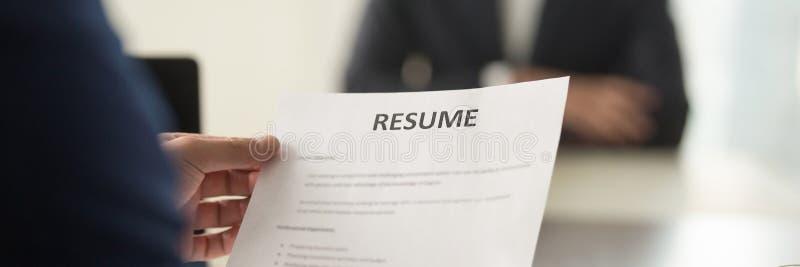 Изображение кандидатуры вакансии cv резюма удерживания босса бумажное интервьюируя панорамное стоковое изображение