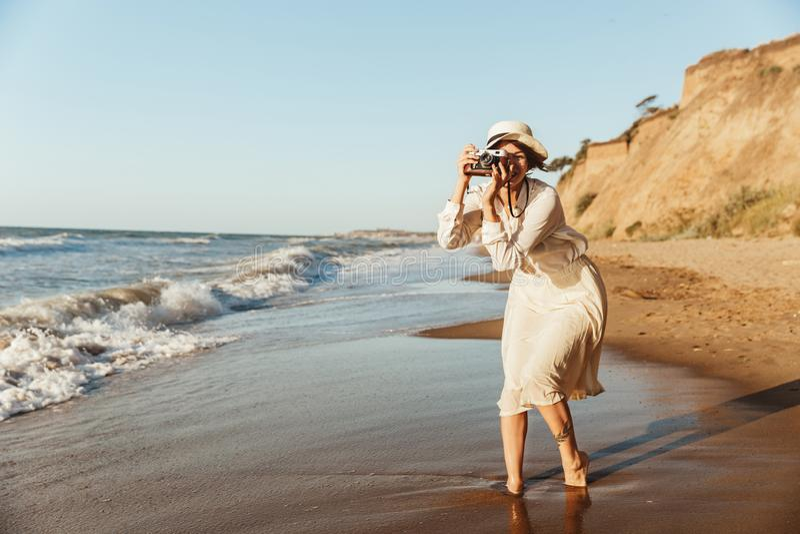 Изображение красивой женщины 20s фотографируя на ретро камере, пока идущ взморьем стоковая фотография rf