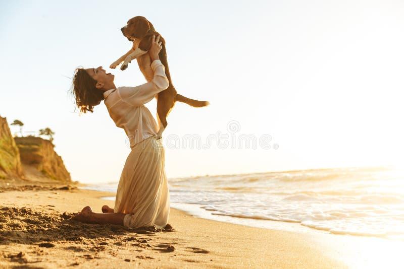 Изображение шикарной женщины 20s обнимая ее собаку, пока сидящ на песке взморьем стоковые фото