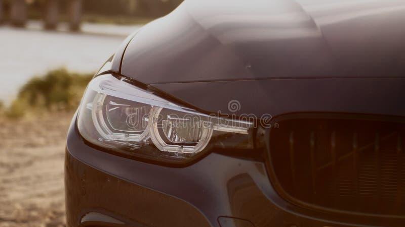Изображение фары и гриля BMW на заходе солнца стоковые фотографии rf