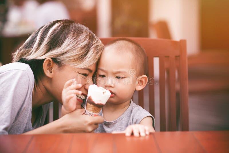 Изображения азиатских женщин есть мороженое с ее сыном стоковое изображение