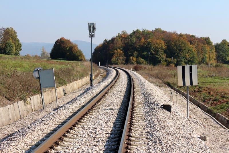 Изогнутые железнодорожные пути окруженные со множественными знаками и железнодорожными светами сигнала с гравием и плотным лесом стоковое фото