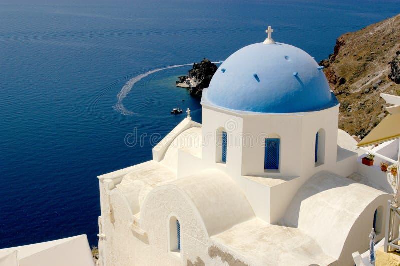 Иконическая голубая церковь купола на Santorini и захватывающие виды над эгейским океаном стоковые фото